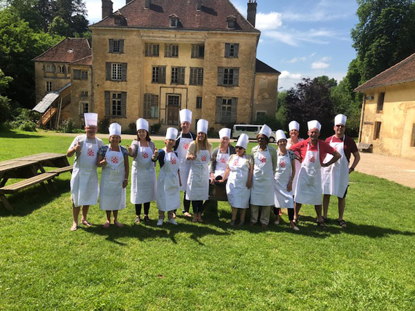 A group of people in chef's hats holding a glass up to celebrate learning to cook in France