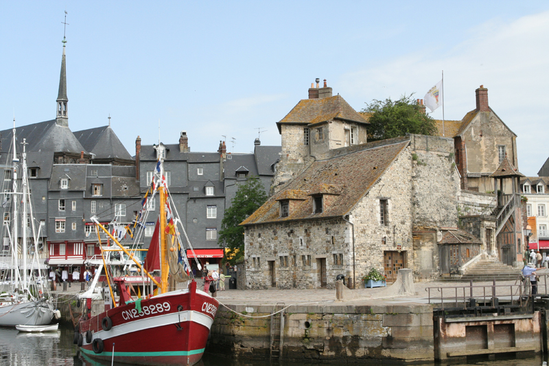 Boat in a tiny harbour, ancient stone buildings in the background at Honfleur