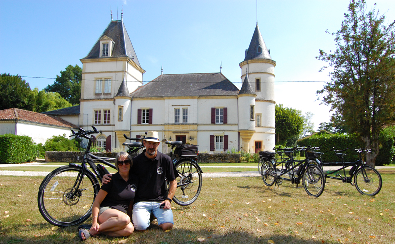 Man and woman pose in front of a French chateau with tandem bikes