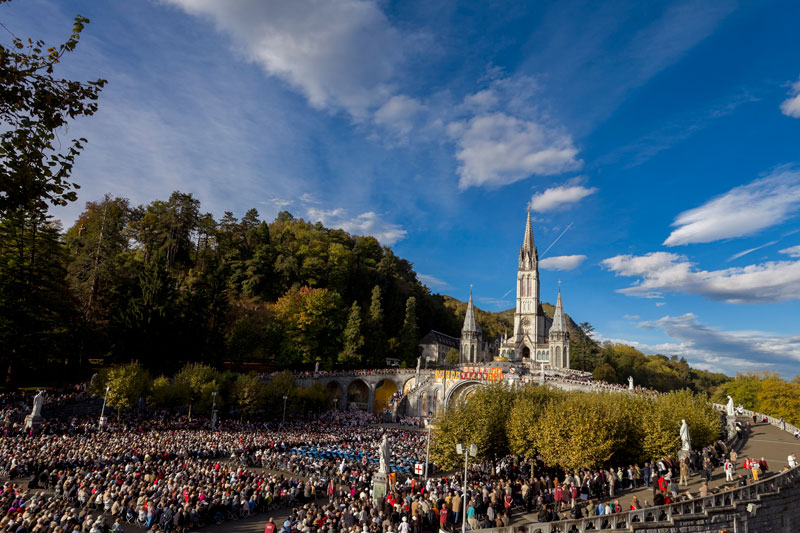 A huge square filled with people at Lourdes in France with church spires in the background