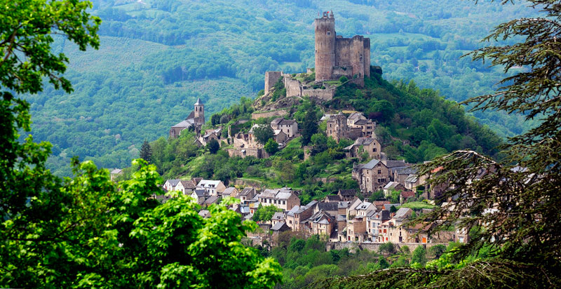 A castle with a tall straight tower on a hill surrounded by forests like a fairy tale in Najac, Aveyron