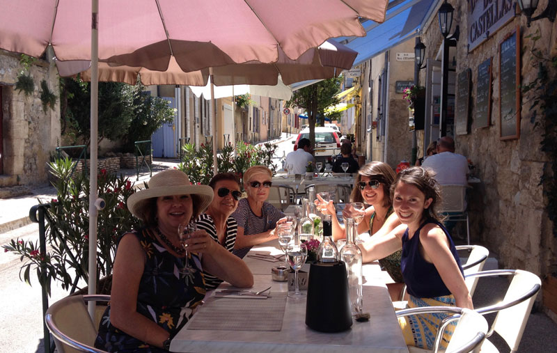 Group of women raising glasses and enjoying a meal in a pretty French terraced cafe