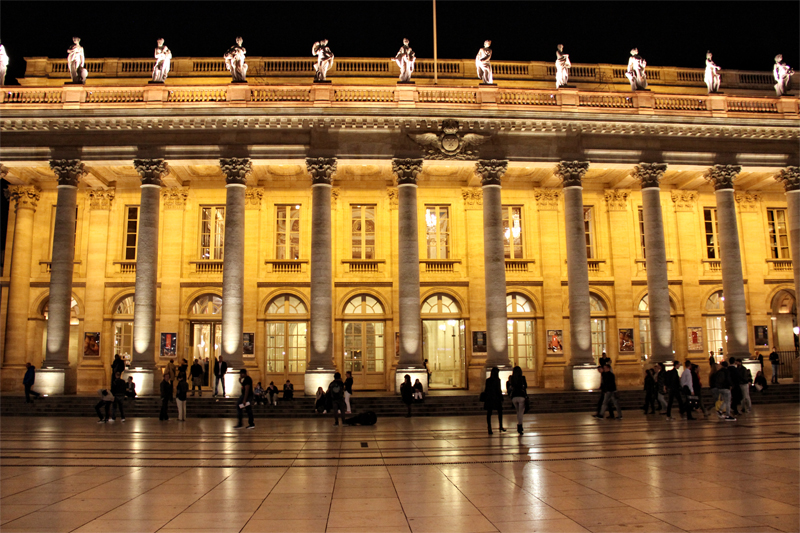 The Grand Opera House of Bordeaux, columns and statues line the front, lit up at night