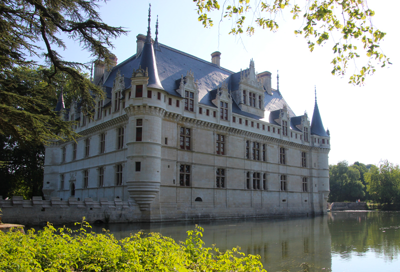 The Chateau of Azay-le-Rideau in the Loire Valley with pointed turrets on the banks of a river