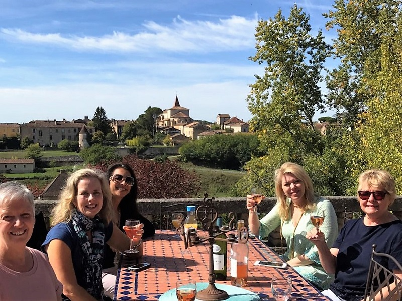 Women raising glasses of rose wine in a vineyard with ancient towers and houses behind them