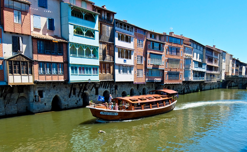 A boat cruising along a river lined with houses in Castres, France