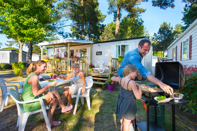 Man, woman and children in the garden of a chalet at a camping site enjoying a barbecue in the sun