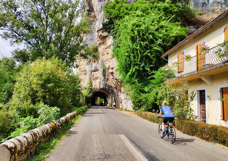 Cyclist going through a tunnel carved into a rock across a road in the Tarn area of France