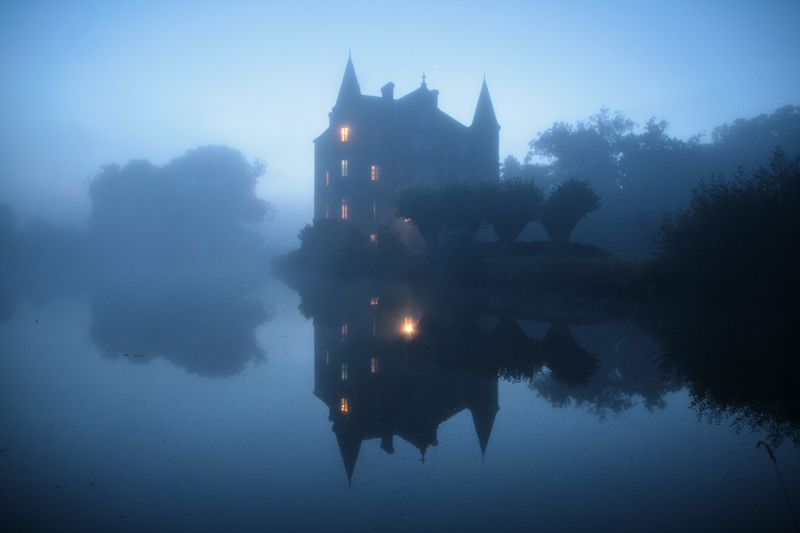 Chateau looms out of the mist on the edge of a lake, it's lights glow and reflect in the water