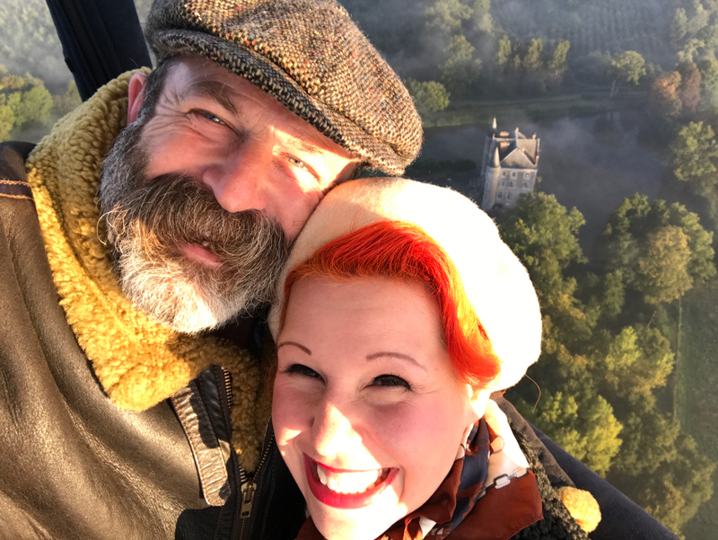 Man and woman smile into camera, in a hot air balloon, below them forests, lakes and a castle