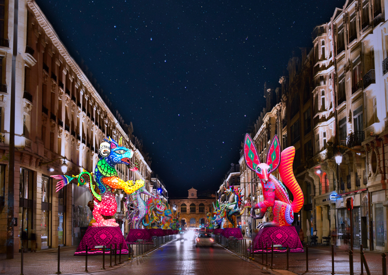 Colourful statues of imaginary animals line a street under a starry sky