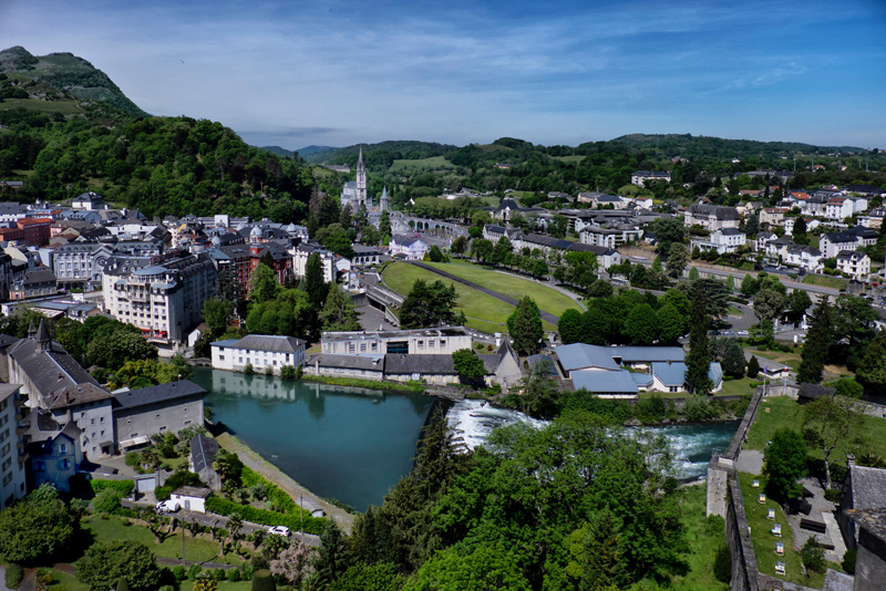 aerial view of Lourdes, a small town with white and grey buildings, churches, surrounded by forests and hills
