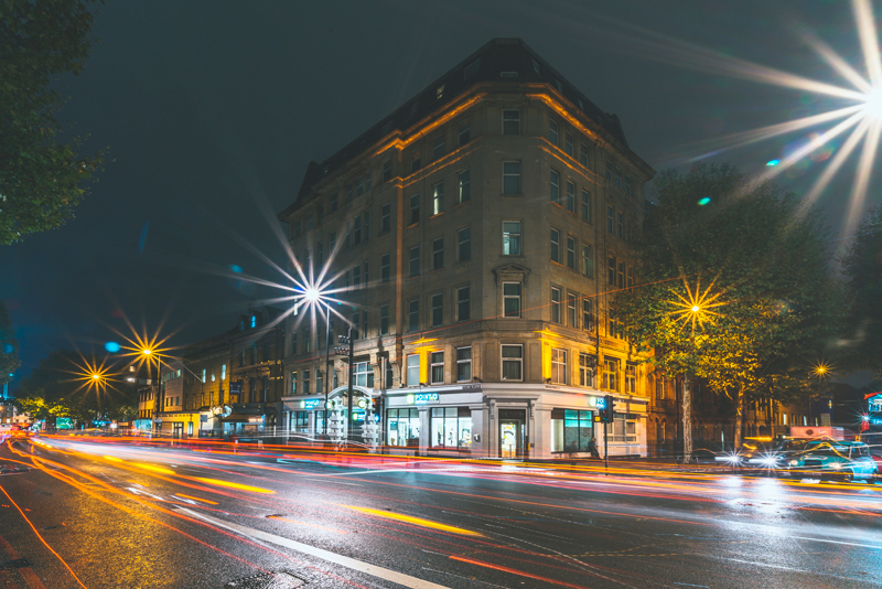 A hotel in an old brick building on the corner of busy cross roads, lit up at night