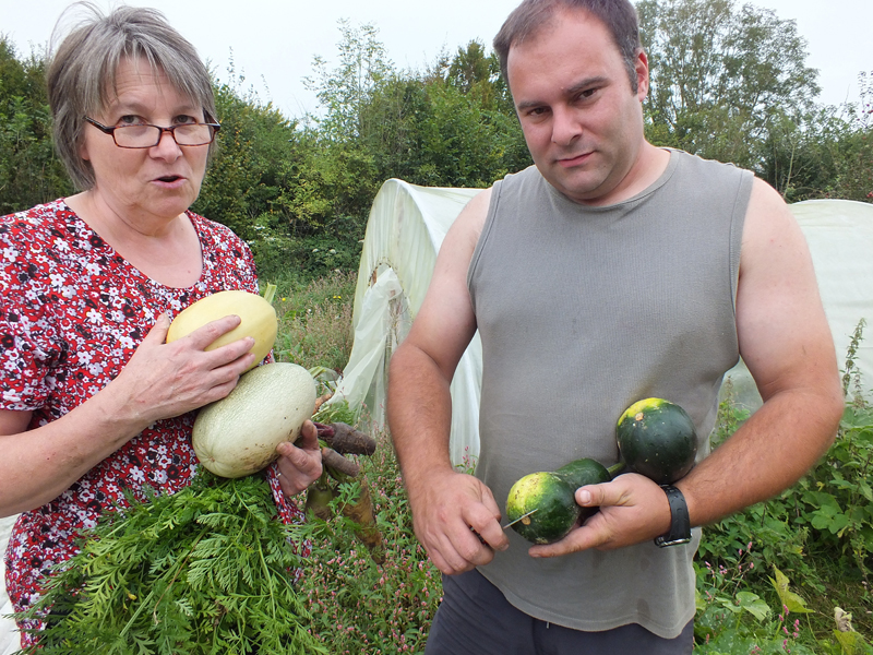Man and woman holding vegetables in a garden that is full of weeds and vegetables