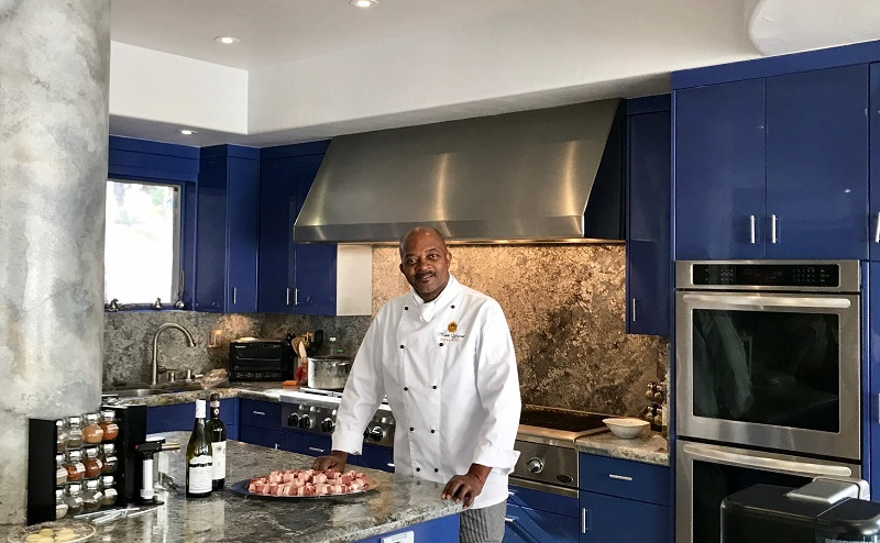 Man in white chef jacket in a beautiful kitchen