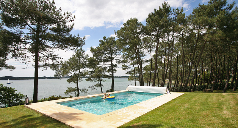 A swimming pool overlooking a beautiful bay surrounded by trees
