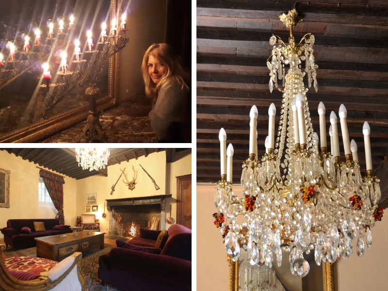 Woman in a room lit by candle and chandelier, the room has a log fire