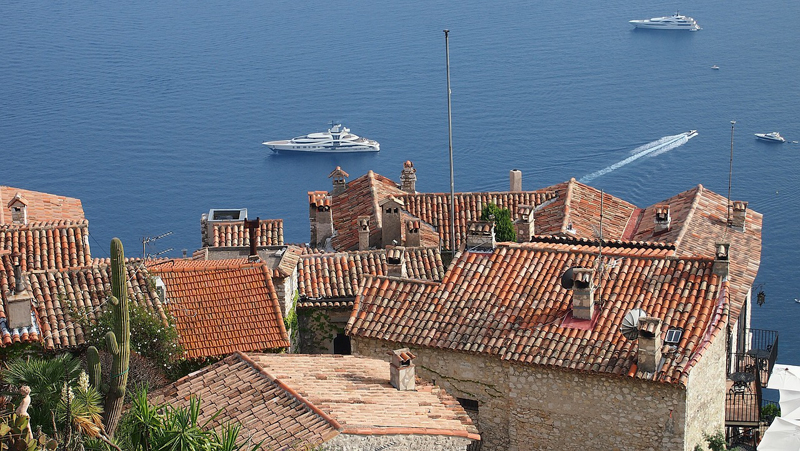 View over the Mediterranean sea from a hill top village over the tops or orange tile roofs