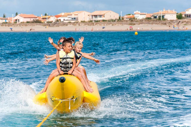 Laughing children on a banana boat in the sea
