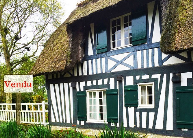 "Half-timbered house with white walls and green wood panels with a ""Sold"" Sign"