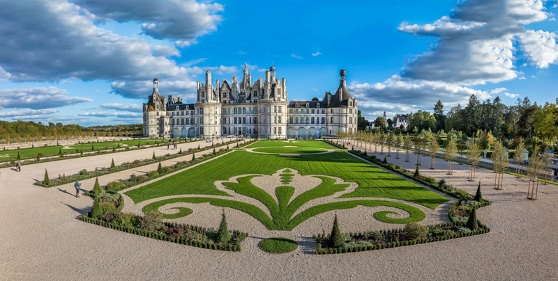 Enormous white stone chateau with many towers, a formal garden in front