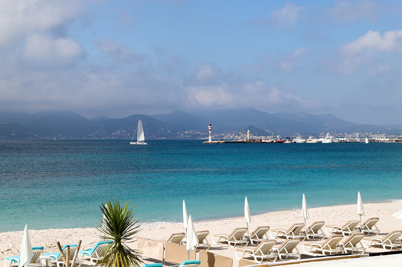 sandy beach with chairs to relax on under a sunny sky, blue water with yacht sailing by