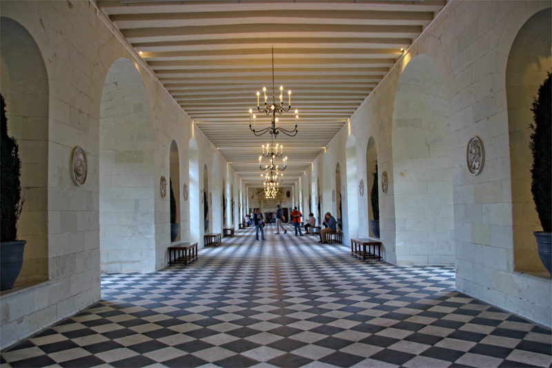 Long gallery with black and white tiled, checked floor, chandeliers hang from the ceiling