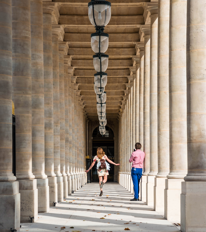 Woman skips along an arcaded street in Paris, lamps above as a man takes a photo