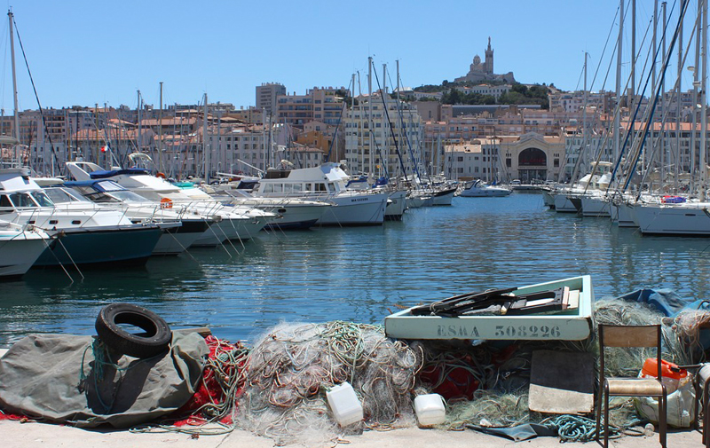 Marseille harbour, lined with posh yachts, in the distance a statue on top of a church on a hill...