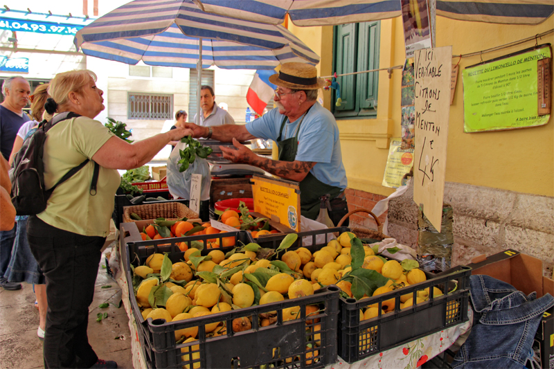 A man in a straw hat sells lemons and oranges from a market stall