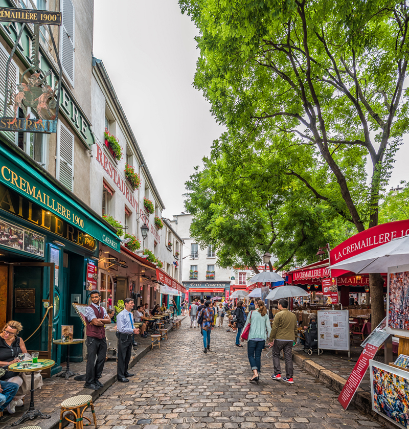 Cobbled street in Montmartre Paris, lined with colourful shops and bars, leafy trees overhang the streets