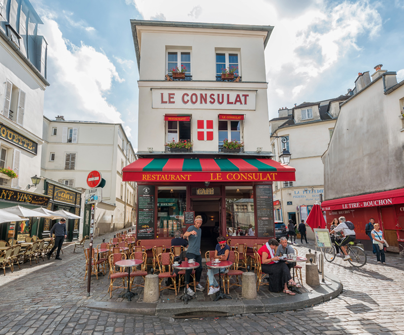 Famous cafe in Montmartre Paris, Le Consulat in a cobbled street, people sit at tables and chairs on the terrace