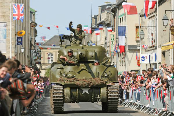 Reconstruction tank with re-enactors in uniform of American WWII cheered on by crowds in a street in Normandy