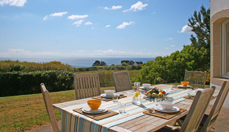 Wooden table laid for breakfast in a garden overlooking a beautiful bay under a blue sky
