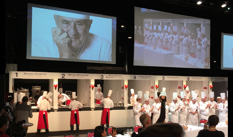 On wide stage, young chefs in white toques cook in a contest in Sarlat