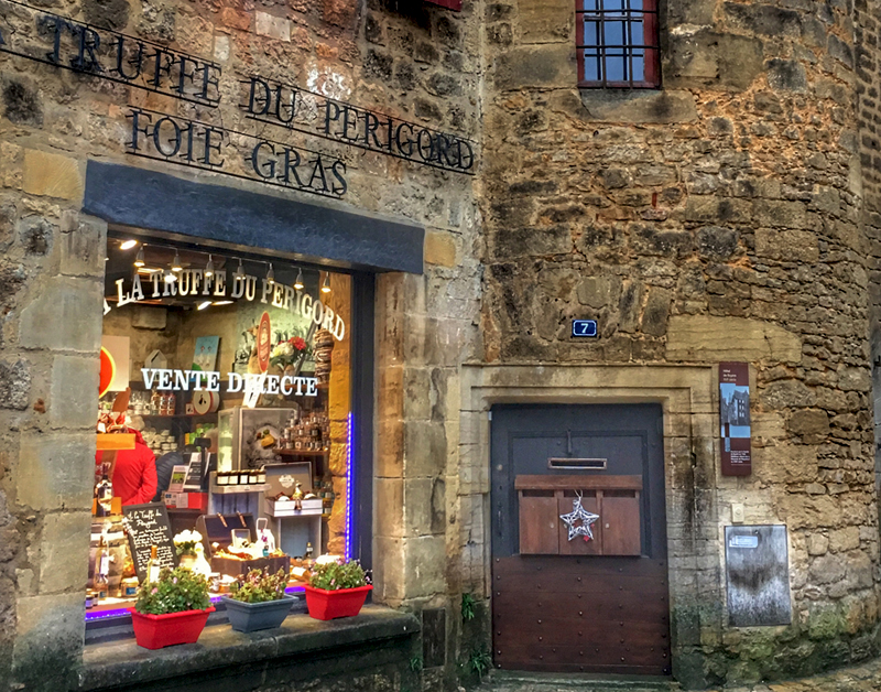 Shop window lit brightly and a tiny wooden door with a single silver star at Christmas in Sarlat, Dordogne