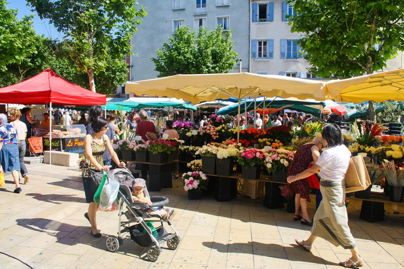 market stalls with colourful awning and people buying flowers from tubs