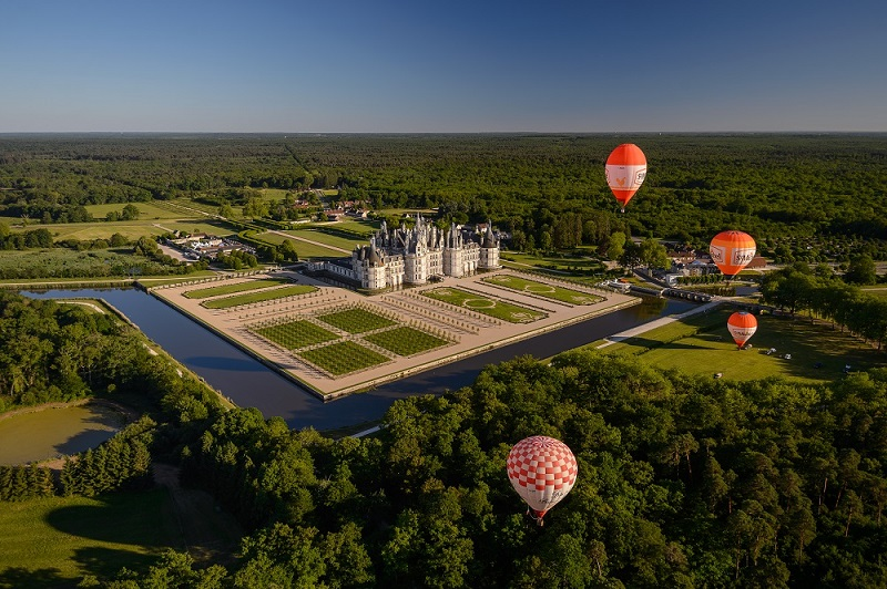 Hot air balloons float over the Chateau de Chambord, clearly showing how it is surrounded on three sides by a moat