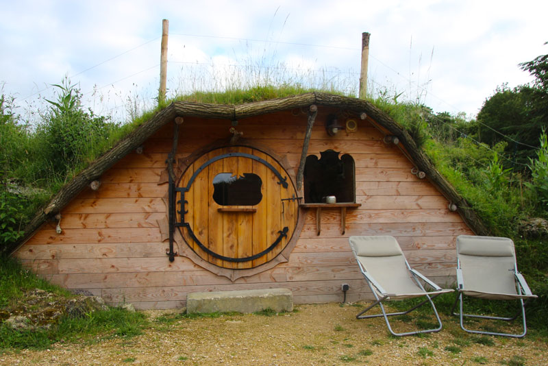 Hobbit style wooden house with a round wooden door