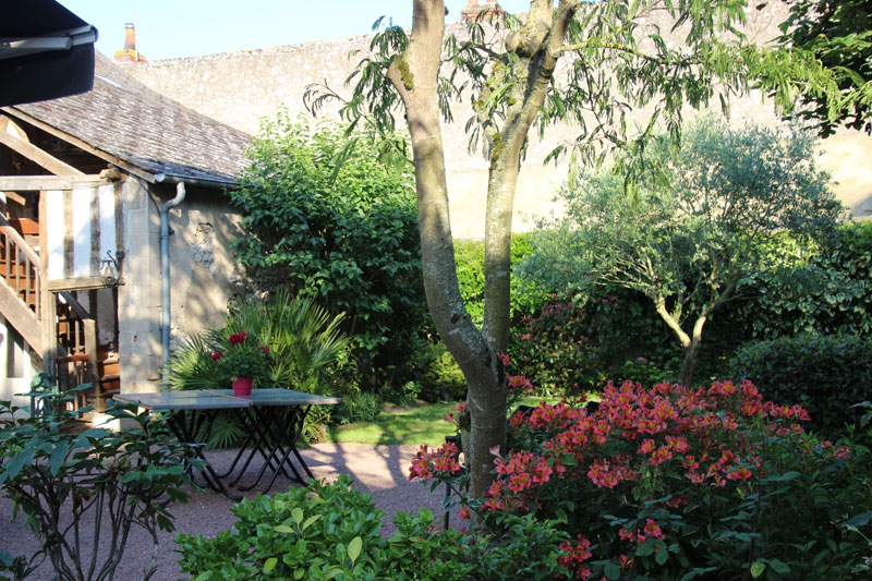 Pretty courtyard garden with lots of flowers and bushes and a table and chairs - so enticing
