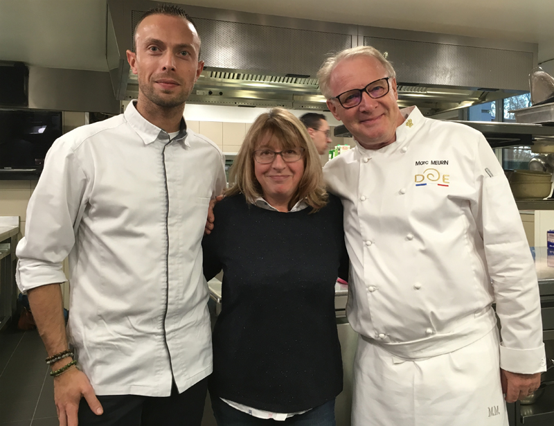 Woman stands with chef on either side all smile
