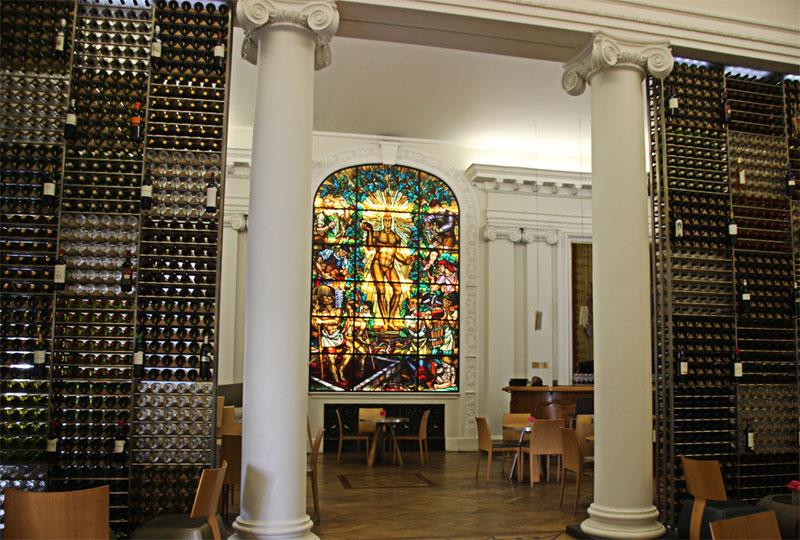 Inside a wine bar in Bordeaux, stained glass windows, huge wine racks
