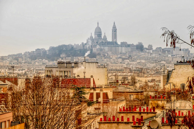 Looking out over the colourful rooftops of Paris, Sacre Coeur church on a hill in the background