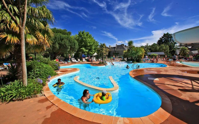 Swimming pool on a campsite in Brittany in which families play under a blue sky, palm trees surround it