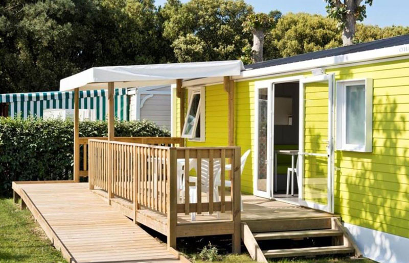 Pretty wooden cottage on a campsite in Sables d'Olonnes, southwest France with stripy awning over a terrace