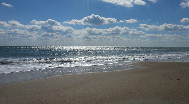 Waves lap a sandy beach under a sky which has clouds in but the sun beams are strong