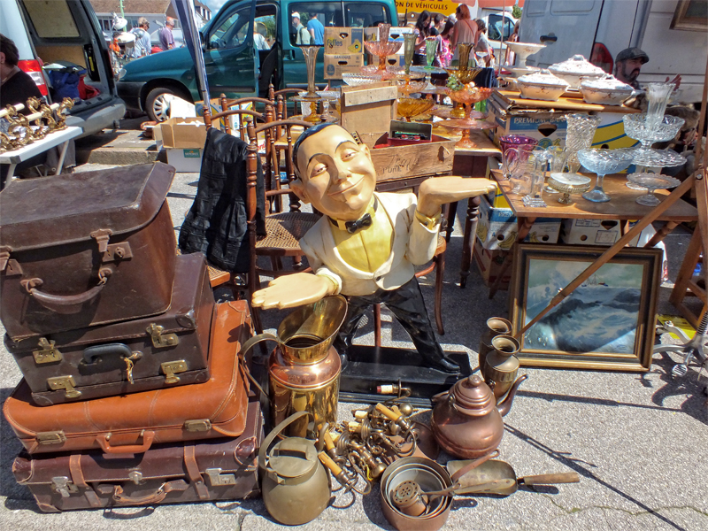 An arrangement of second hand goods including a wooden waiter statue, and antiques at a flea market in France