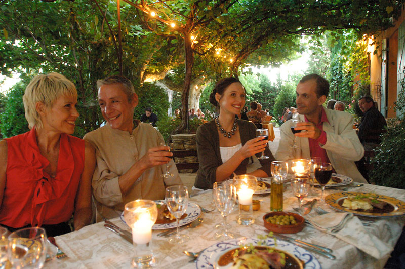 People enjoying themselves at dinner in a beautiful outdoor restaurant in France