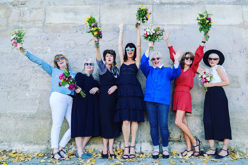 A group of women hold bunches of flowers smiling widely as they enjoy a small group tour of Bordeaux