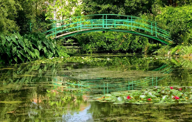 Bright green wooden bridge over a lily pond, similar to the one at Monet's garden in Giverny